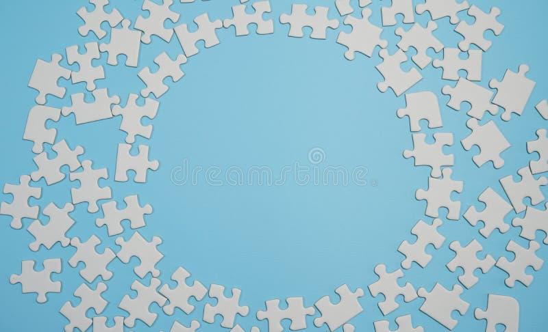 Frammento di un puzzle bianco piegato e un mucchio degli elementi spettinati di puzzle contro lo sfondo di una superficie blu immagine stock libera da diritti