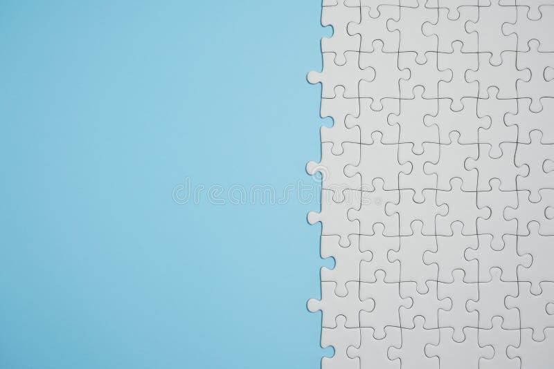 Frammento di un puzzle bianco piegato e un mucchio degli elementi spettinati di puzzle contro lo sfondo di una superficie blu immagini stock libere da diritti