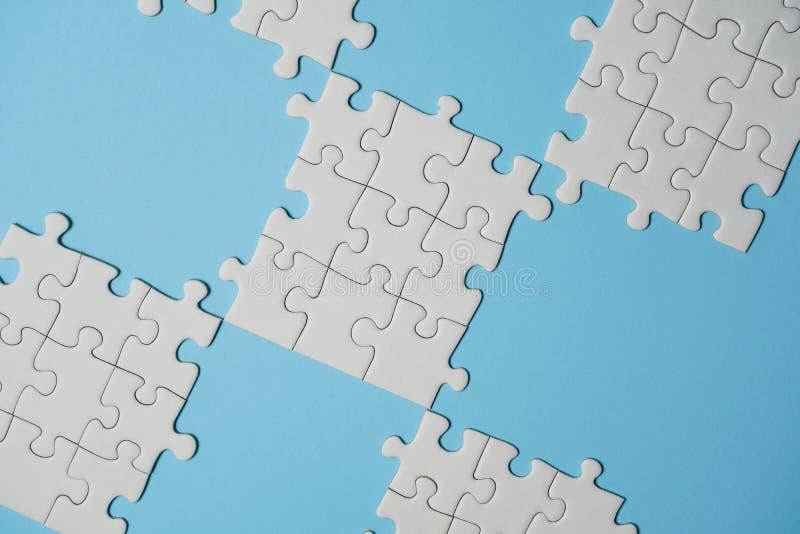 Frammento di un puzzle bianco piegato e un mucchio degli elementi spettinati di puzzle contro lo sfondo di una superficie blu immagini stock