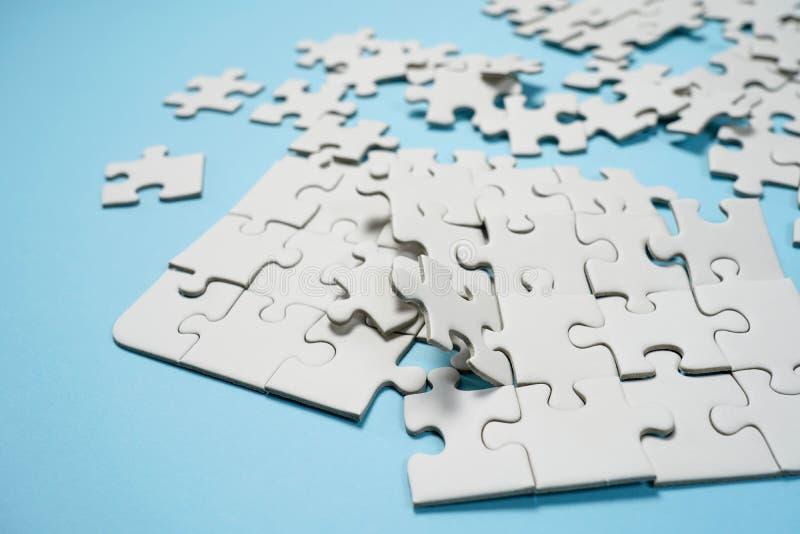Frammento di un puzzle bianco piegato e un mucchio degli elementi spettinati di puzzle contro lo sfondo di una superficie blu immagine stock