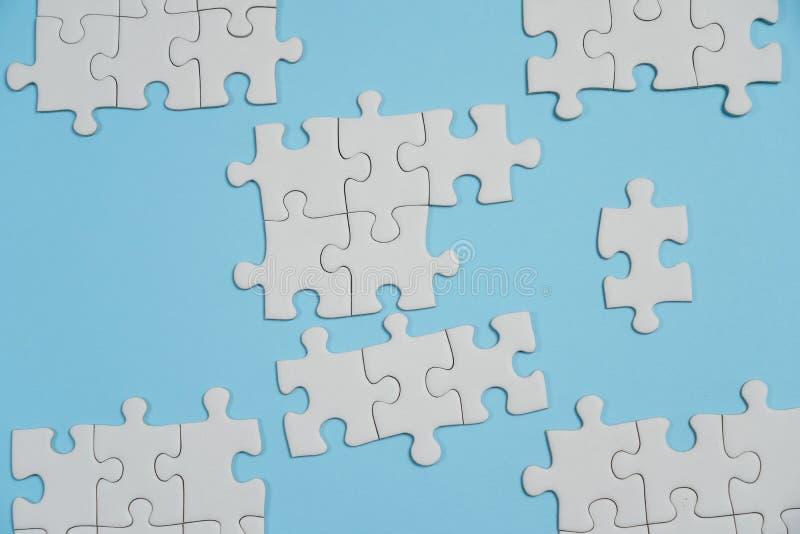 Frammento di un puzzle bianco piegato e un mucchio degli elementi spettinati di puzzle contro lo sfondo di una superficie blu fotografie stock