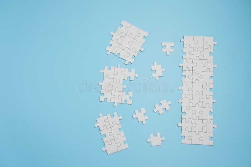 Frammento di un puzzle bianco piegato e un mucchio degli elementi spettinati di puzzle contro lo sfondo di una superficie blu fotografia stock libera da diritti
