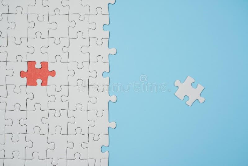 Frammento di un puzzle bianco piegato e un mucchio degli elementi spettinati di puzzle contro lo sfondo di una superficie blu fotografie stock libere da diritti