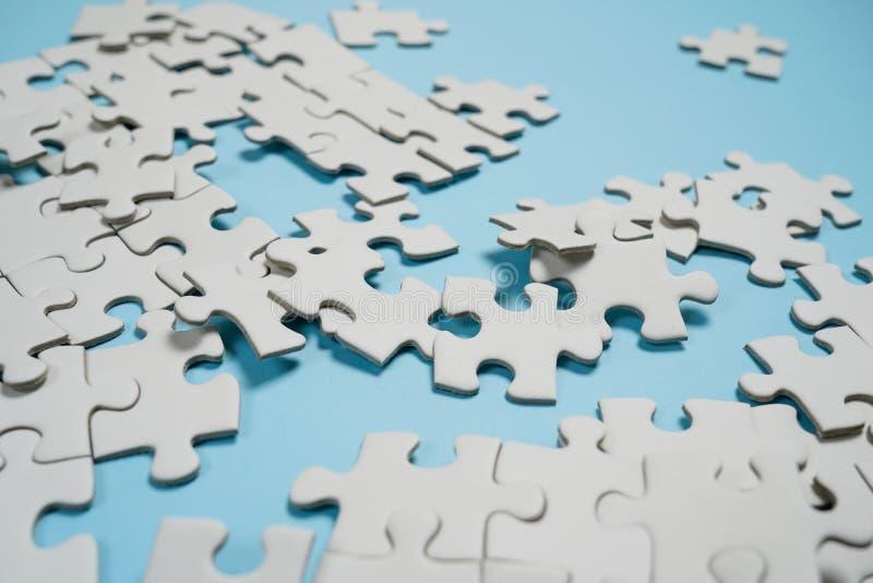 Frammento di un puzzle bianco piegato e un mucchio degli elementi spettinati di puzzle contro lo sfondo di una superficie blu fotografia stock