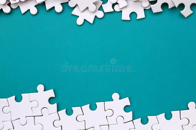 Frammento di un puzzle bianco piegato e un mucchio degli elementi spettinati di puzzle contro lo sfondo di una superficie blu Str immagine stock