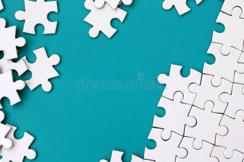 Frammento di un puzzle bianco piegato e un mucchio degli elementi spettinati di puzzle contro lo sfondo di una superficie blu Str fotografia stock