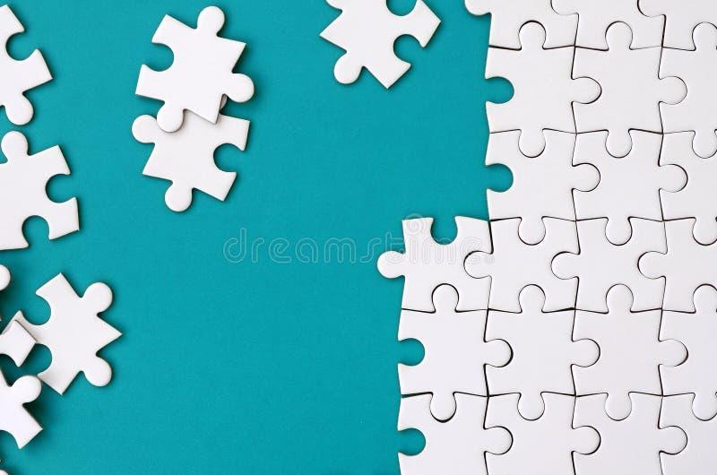 Frammento di un puzzle bianco piegato e un mucchio degli elementi spettinati di puzzle contro lo sfondo di una superficie blu Str immagini stock libere da diritti
