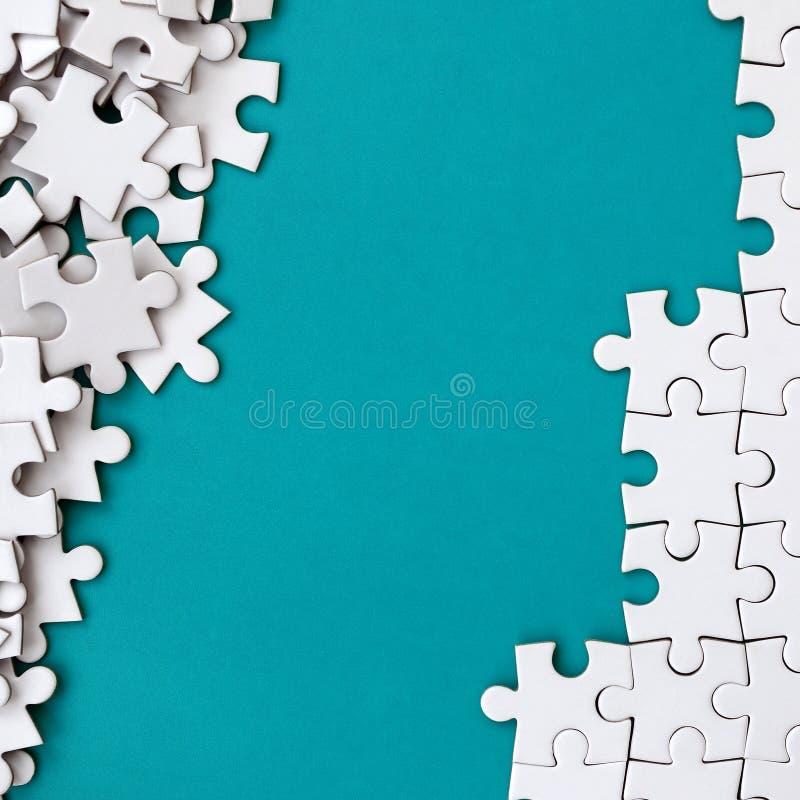 Frammento di un puzzle bianco piegato e un mucchio degli elementi spettinati di puzzle contro lo sfondo di una superficie blu Str fotografia stock libera da diritti