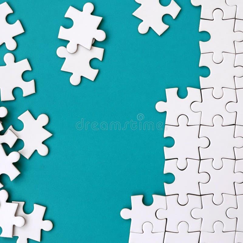 Frammento di un puzzle bianco piegato e un mucchio degli elementi spettinati di puzzle contro lo sfondo di una superficie blu Str fotografie stock libere da diritti