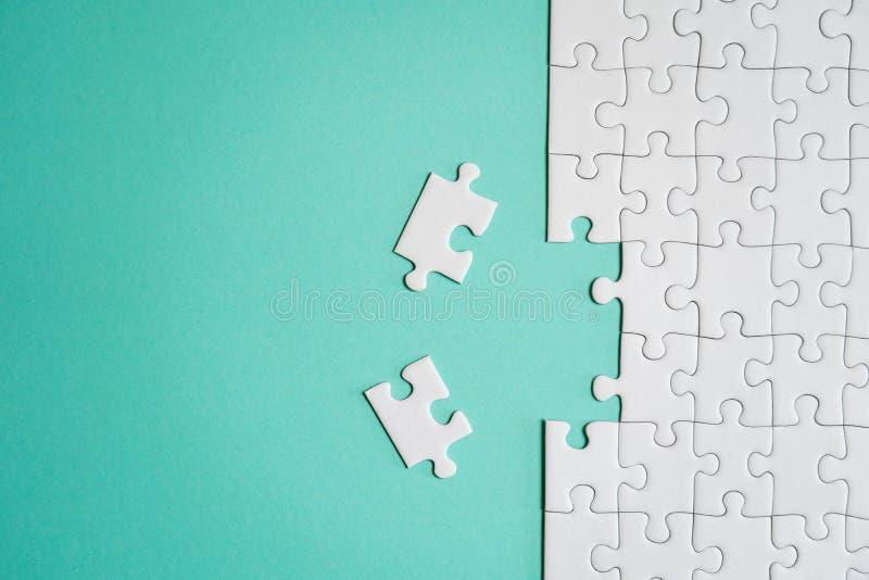 Frammento di un puzzle bianco piegato e un mucchio degli elementi spettinati di puzzle contro lo sfondo di una superficie colorat fotografie stock libere da diritti