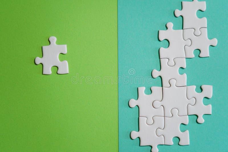 Frammento di un puzzle bianco piegato e un mucchio degli elementi spettinati di puzzle contro lo sfondo di una superficie colorat fotografia stock libera da diritti