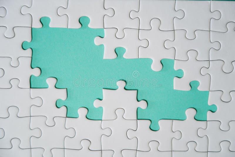 Frammento di un puzzle bianco piegato e un mucchio degli elementi spettinati di puzzle contro lo sfondo di una superficie colorat fotografia stock