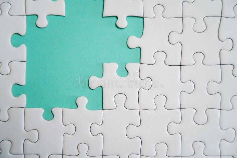 Frammento di un puzzle bianco piegato e un mucchio degli elementi spettinati di puzzle contro lo sfondo di una superficie colorat immagini stock libere da diritti