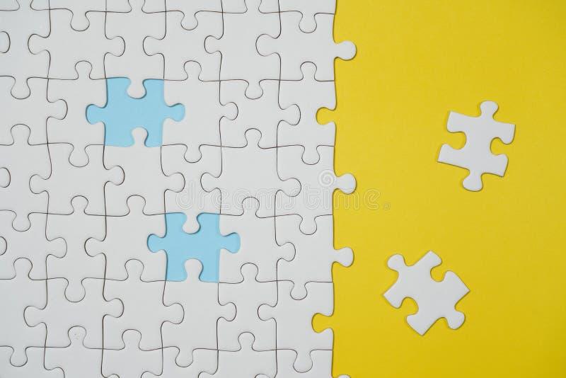 Frammento di un puzzle bianco piegato e un mucchio degli elementi spettinati di puzzle contro lo sfondo di una superficie gialla fotografie stock libere da diritti