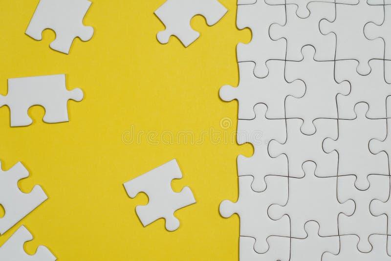 Frammento di un puzzle bianco piegato e un mucchio degli elementi spettinati di puzzle contro lo sfondo di una superficie gialla immagini stock libere da diritti