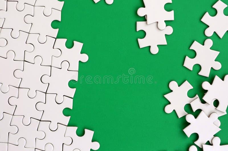 Frammento di un puzzle bianco piegato e un mucchio degli elementi spettinati di puzzle contro lo sfondo di una superficie verde S fotografia stock