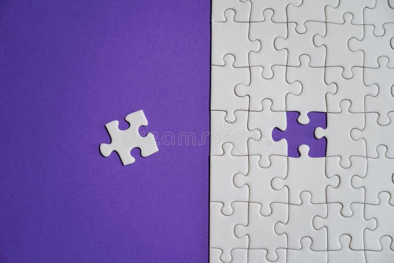 Frammento di un puzzle bianco piegato e un mucchio degli elementi spettinati di puzzle contro lo sfondo di una superficie viola fotografia stock libera da diritti