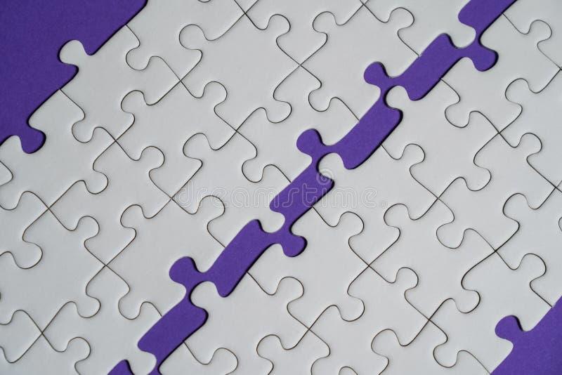 Frammento di un puzzle bianco piegato e un mucchio degli elementi spettinati di puzzle contro lo sfondo di una superficie viola immagini stock
