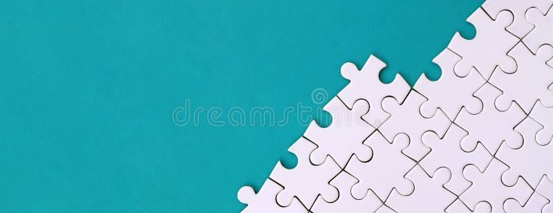 Frammento di un puzzle bianco piegato sui precedenti di una superficie blu della plastica Foto di struttura con lo spazio della c immagine stock