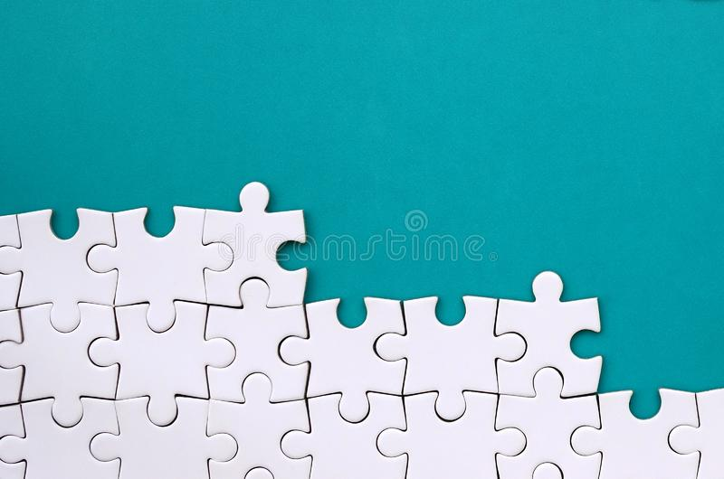 Frammento di un puzzle bianco piegato sui precedenti di una superficie blu della plastica Foto di struttura con lo spazio della c fotografia stock libera da diritti