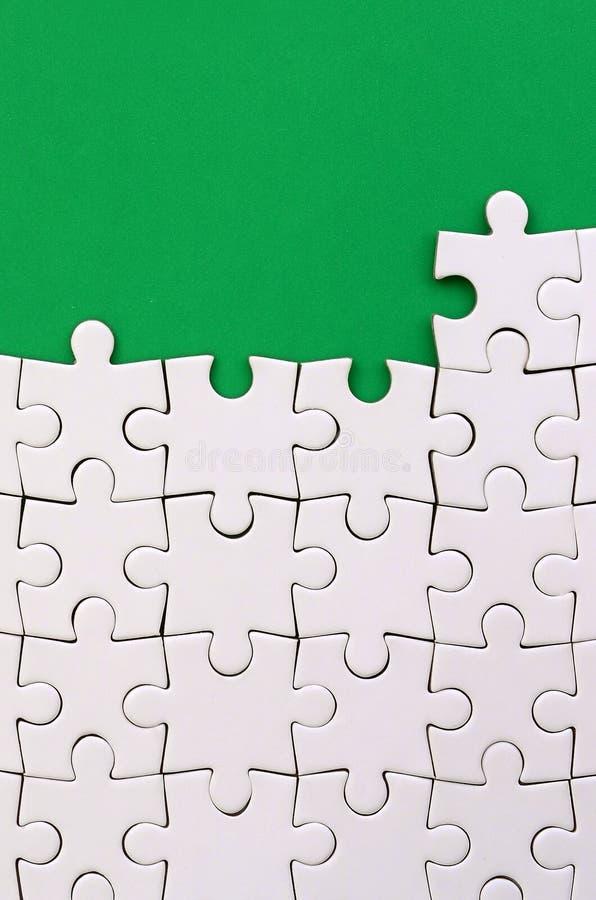 Frammento di un puzzle bianco piegato sui precedenti di una superficie verde della plastica Foto di struttura con lo spazio della fotografie stock libere da diritti