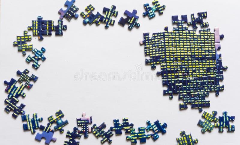 Frammento di un puzzle piegato e un mucchio degli elementi spettinati di puzzle contro i precedenti bianchi Foto con spazio fotografie stock libere da diritti