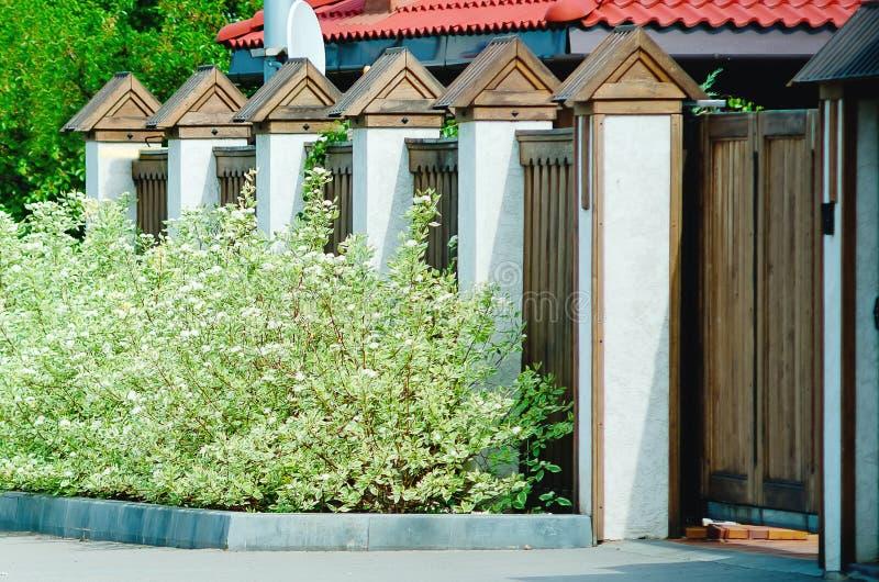 Frammento di un recinto moderno marrone di legno con le colonne finite con la pietra, primo piano Recinto di legno Ideas di proge immagini stock libere da diritti