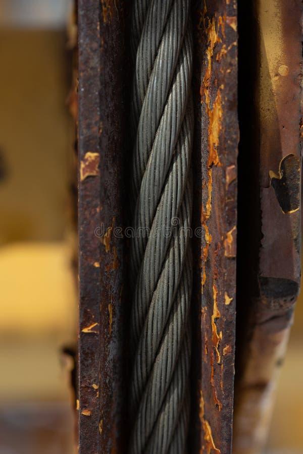 Frammento di vecchia attrezzatura per l'edilizia arrugginita con un forte cavo dell'acciaio del metallo fotografie stock
