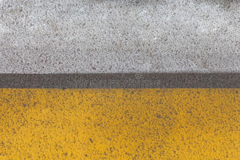 Frammento giallo astratto della segnaletica stradale con sollievo della pista della gomma sopra immagini stock libere da diritti