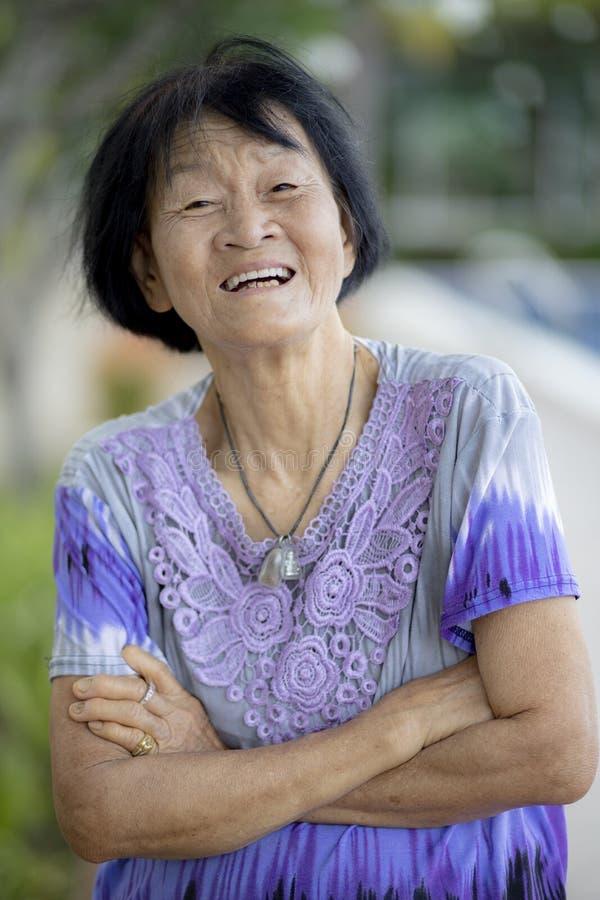 Framsida av den asiatiska höga kvinnan som skrattar med lyckasinnesrörelse royaltyfria foton