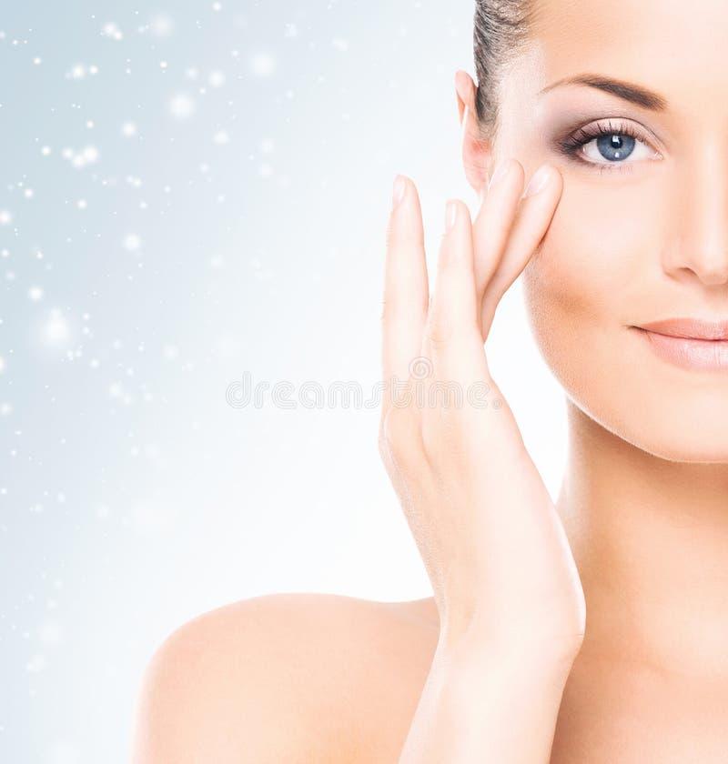 Framsida av den attraktiva och sunda kvinnan över säsongsbetonad julbakgrund med snöflingor för en vinter Sjukvård, brunnsort, ma fotografering för bildbyråer