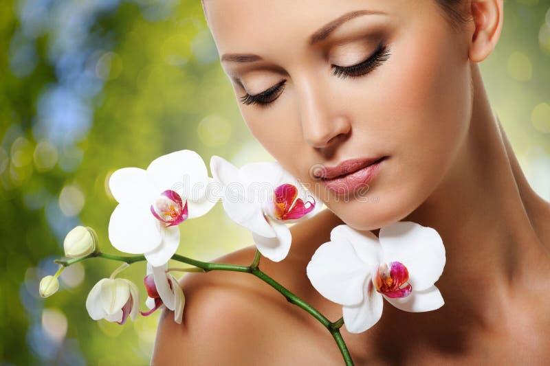 Framsida av den härliga kvinnan med en vit orkidéblomma royaltyfri foto