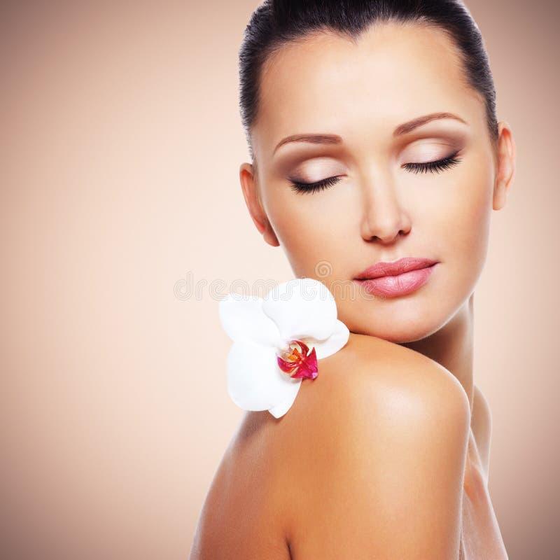 Framsida av den härliga kvinnan med en vit orkidéblomma arkivfoton