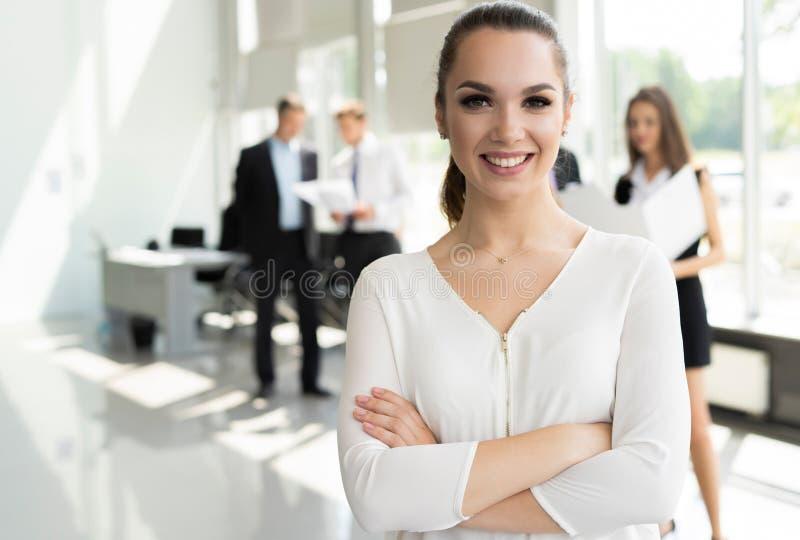 Framsida av den härliga kvinnan på bakgrunden av affärsfolk royaltyfri bild