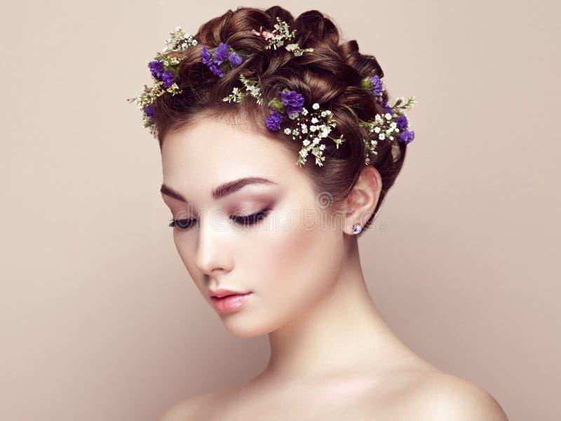 Framsida av den härliga kvinnan som dekoreras med blommor arkivbild