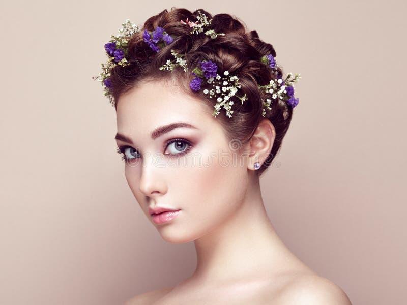 Framsida av den härliga kvinnan som dekoreras med blommor royaltyfri foto