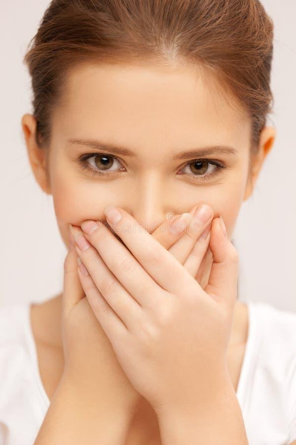 Framsida av den härliga tonårs- flickan som täcker hennes mun royaltyfri foto