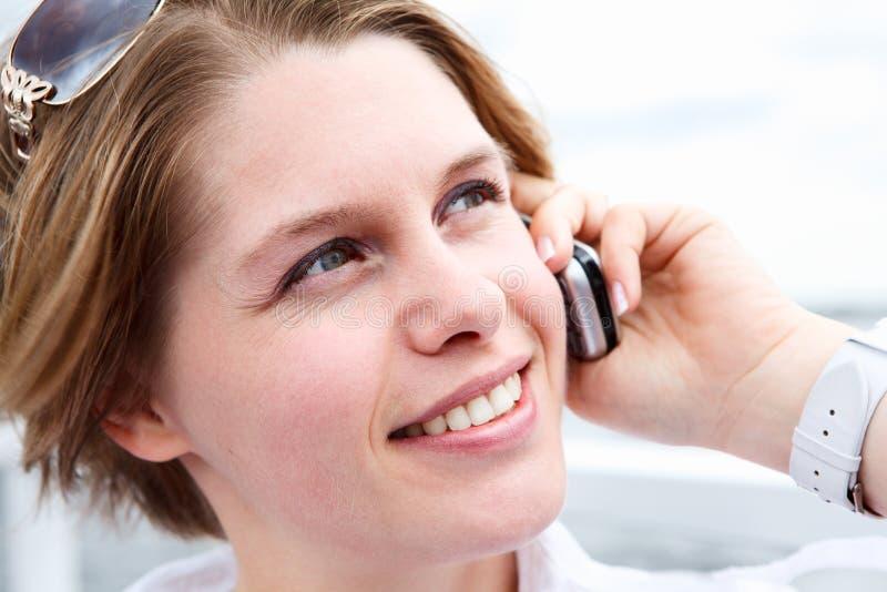 Framsida av den lyckliga kvinnan med solglasögon som kallar på mobil royaltyfria bilder