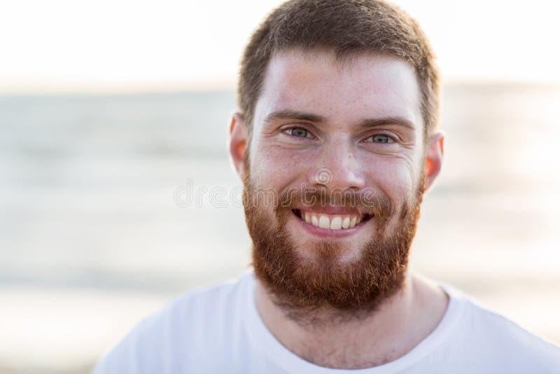 Framsida av den lyckliga le unga mannen på stranden arkivbilder