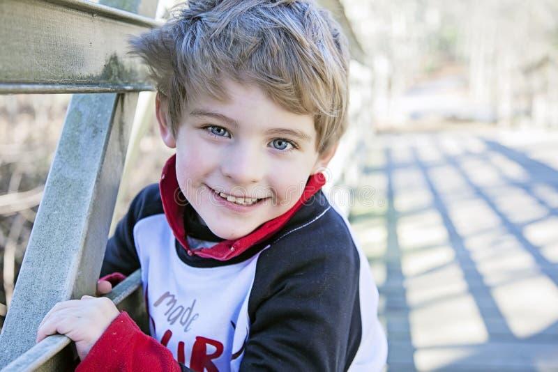 Framsida av den lyckliga pojken som utanför spelar fotografering för bildbyråer