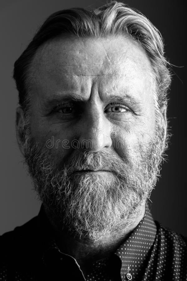Framsida av den mogna skäggiga mannen i svartvitt royaltyfria foton