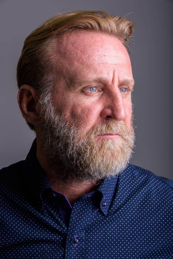 Framsida av den mogna skäggiga mannen som tänker i grå bakgrund fotografering för bildbyråer