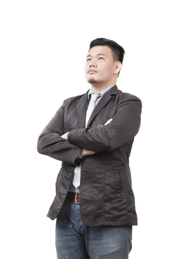 Framsida av den unga asiatiska mannen som bär västra dräktanseende och lookin royaltyfria foton