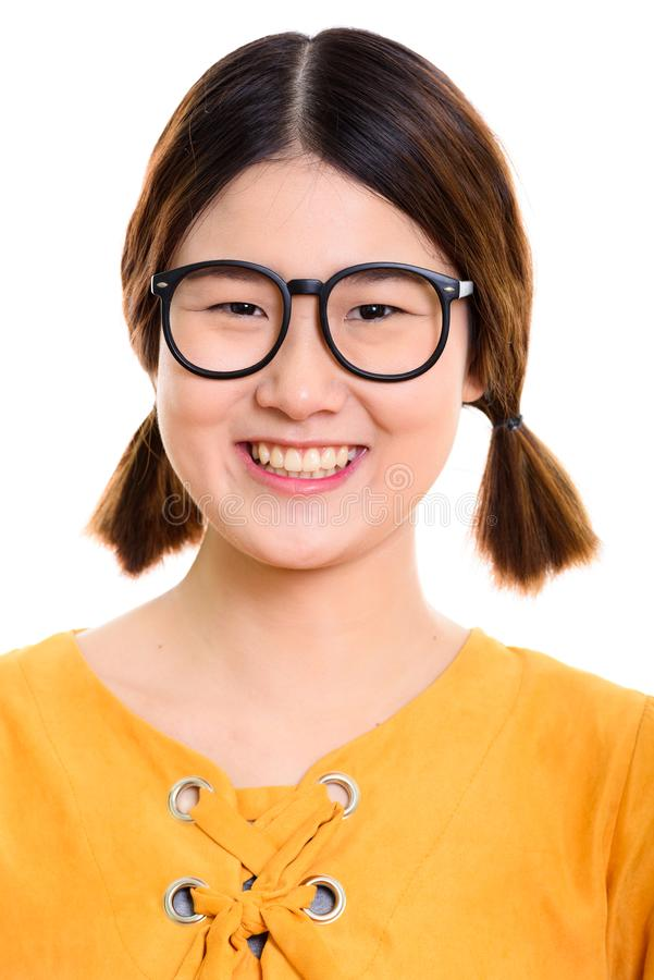 Framsida av den unga lyckliga asiatiska kvinnan som ler, medan bära glasögon royaltyfria foton