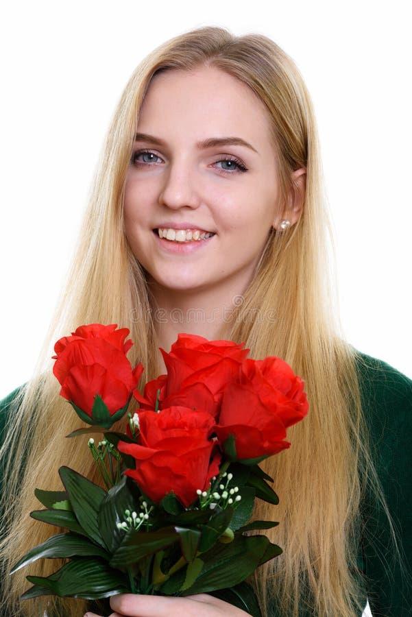 Framsida av den unga lyckliga tonårs- flickan som ler, medan rymma röda rosor arkivfoto