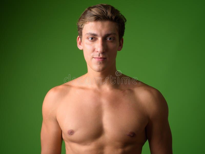 Framsida av den unga stiliga shirtless mannen som ser kameran royaltyfri foto