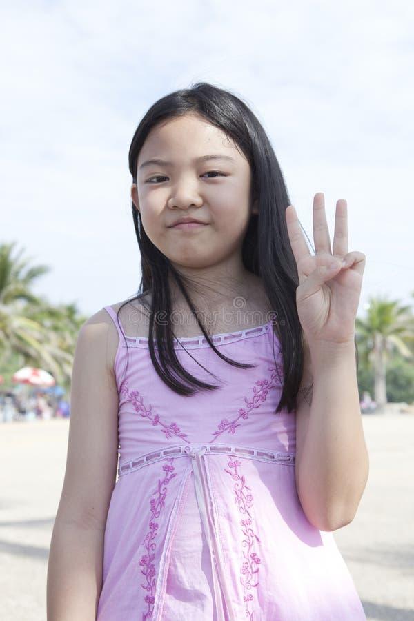 Framsida av det asiatiska flickashowfingret som agerar som ett symboliskt av numret royaltyfri fotografi