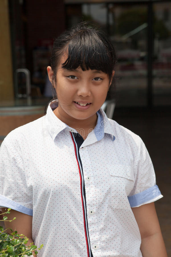 Framsida av det asiatiska tonåriga åldriga anseendet med att le framsidan arkivfoton