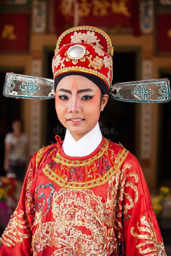 Framsida av en härlig kinesisk operaaktris med framsidamålning, ståenderiktning, närbild, suddiga bakgrunder Trat landskap, royaltyfri bild