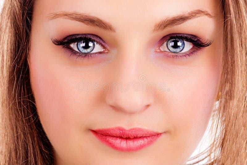 Framsida av en härlig ung kvinna med blåa ögon arkivfoton